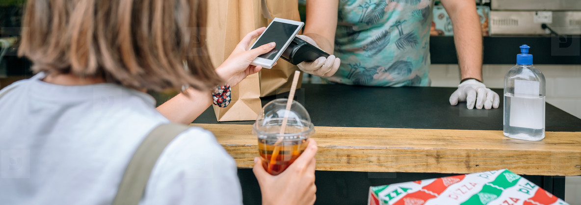 Woman paying with mobile a take away order