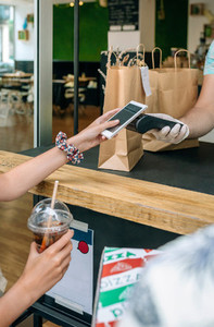 Unrecognizable woman paying with mobile a take away order