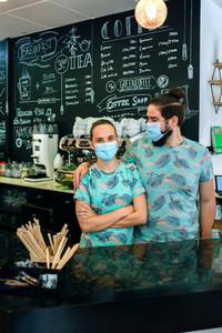 Coffee shop owners posing with masks