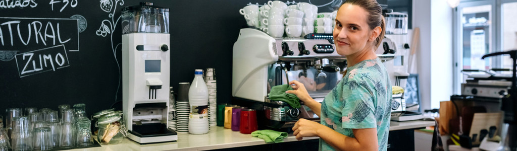 Smiling waitress cleaning coffee maker