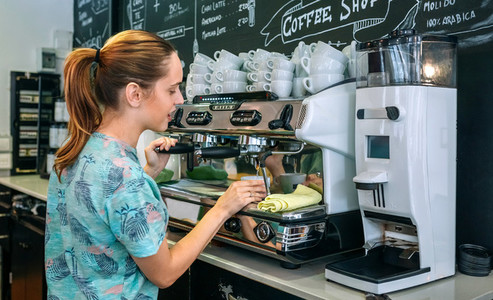 Female barista preparing coffee machine