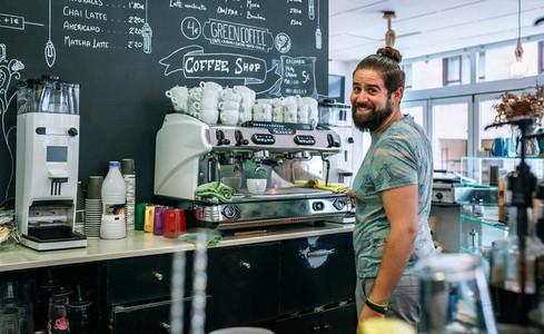 Male barista preparing coffee machine