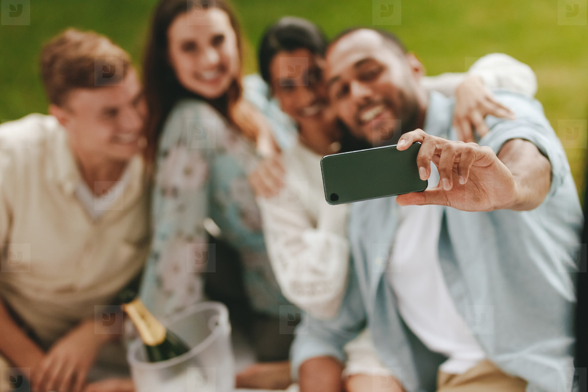 Group of young people on picnic taking a selfie