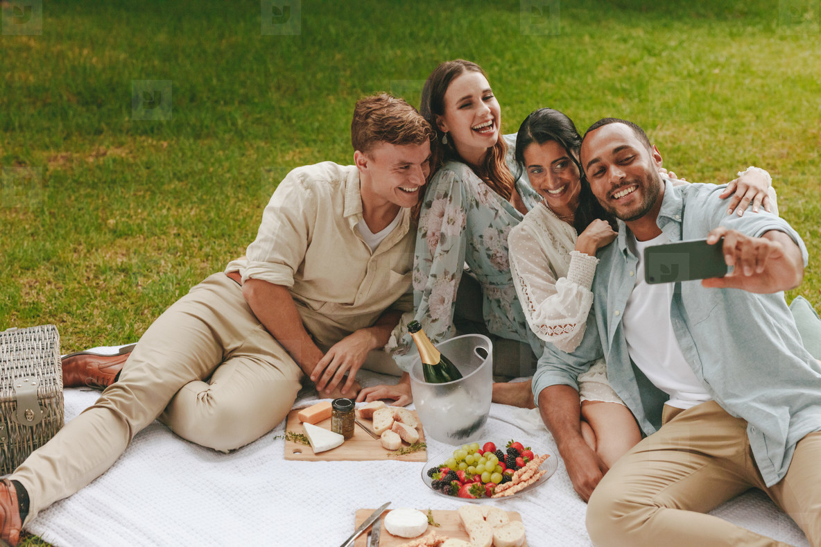 Group of friends taking selfie at picnic