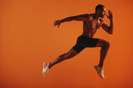 Muscular athlete running on orange background