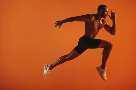 Muscular athlete running on orange background