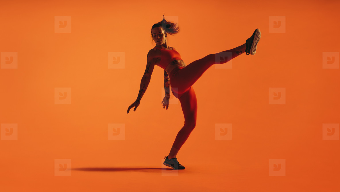 Fit woman doing leg stretches on orange background