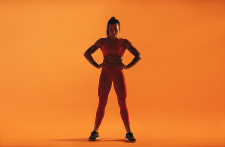 Fit woman standing against orange background