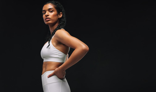 Side view portrait of fit woman on black background