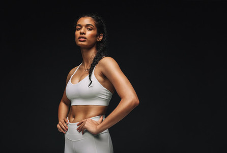Portrait of fit woman on black background