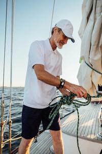 Mature yachtsman adjusting rope