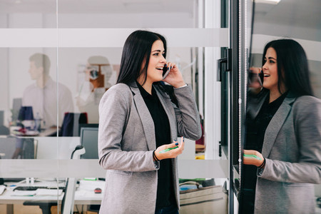 A businesswoman talking by cellphone near a window in the office