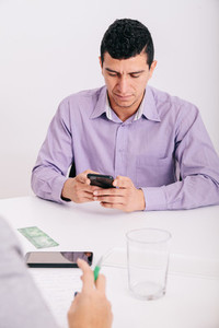 Close up of office worker sitting using his smartphone