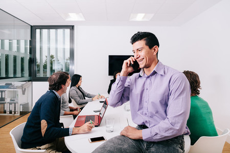 A businessman talking on cell phone sitting at the office table