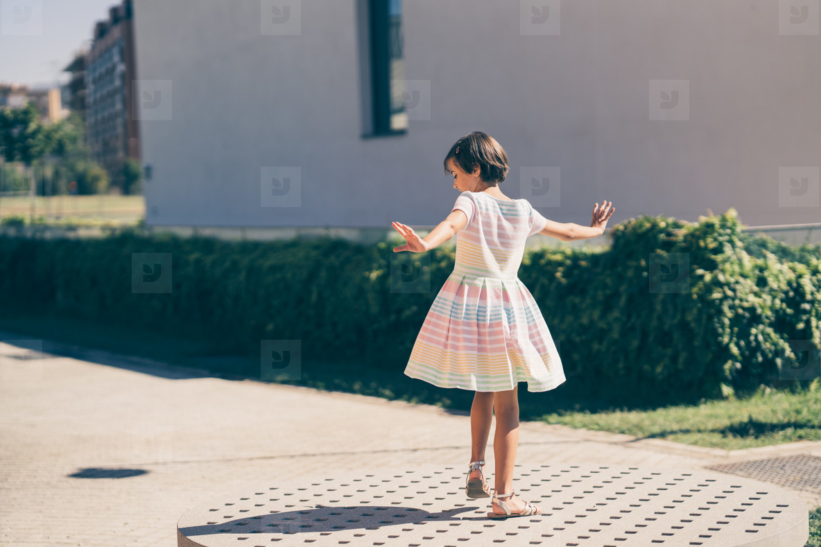 Happy 9 year old girl in a pretty dress playing