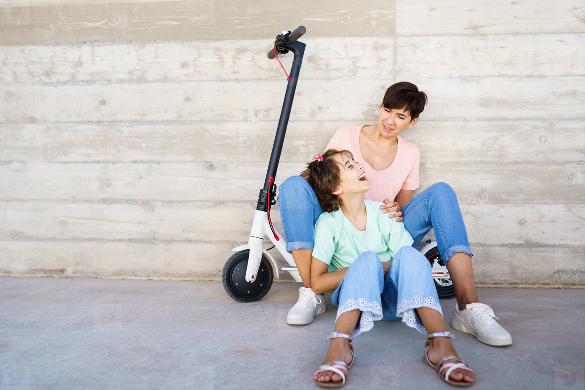 Mother and daughter sitting on an electric scooter