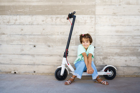 Little girl sitting on an electric scooter in the street