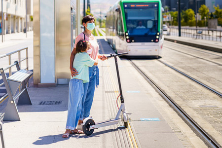 Mother and daughter waiting for the train with an electronic scooter
