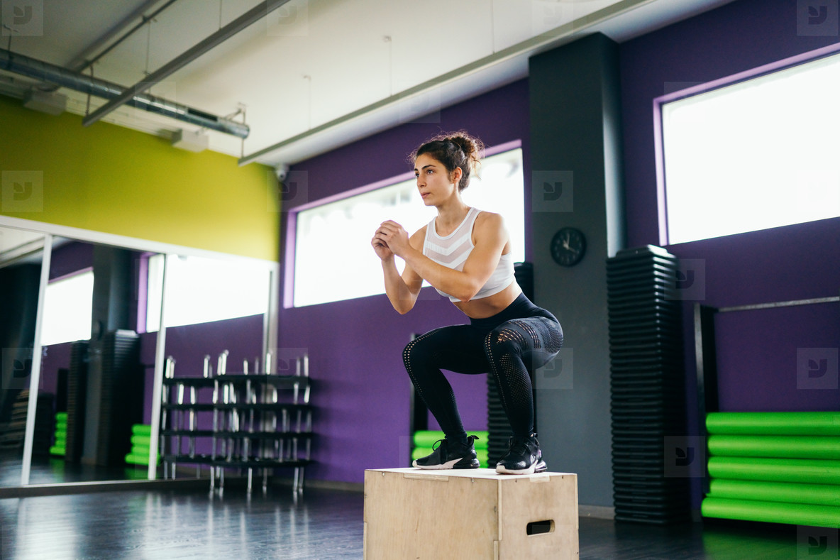 Athletic woman doing squats on box at the gym