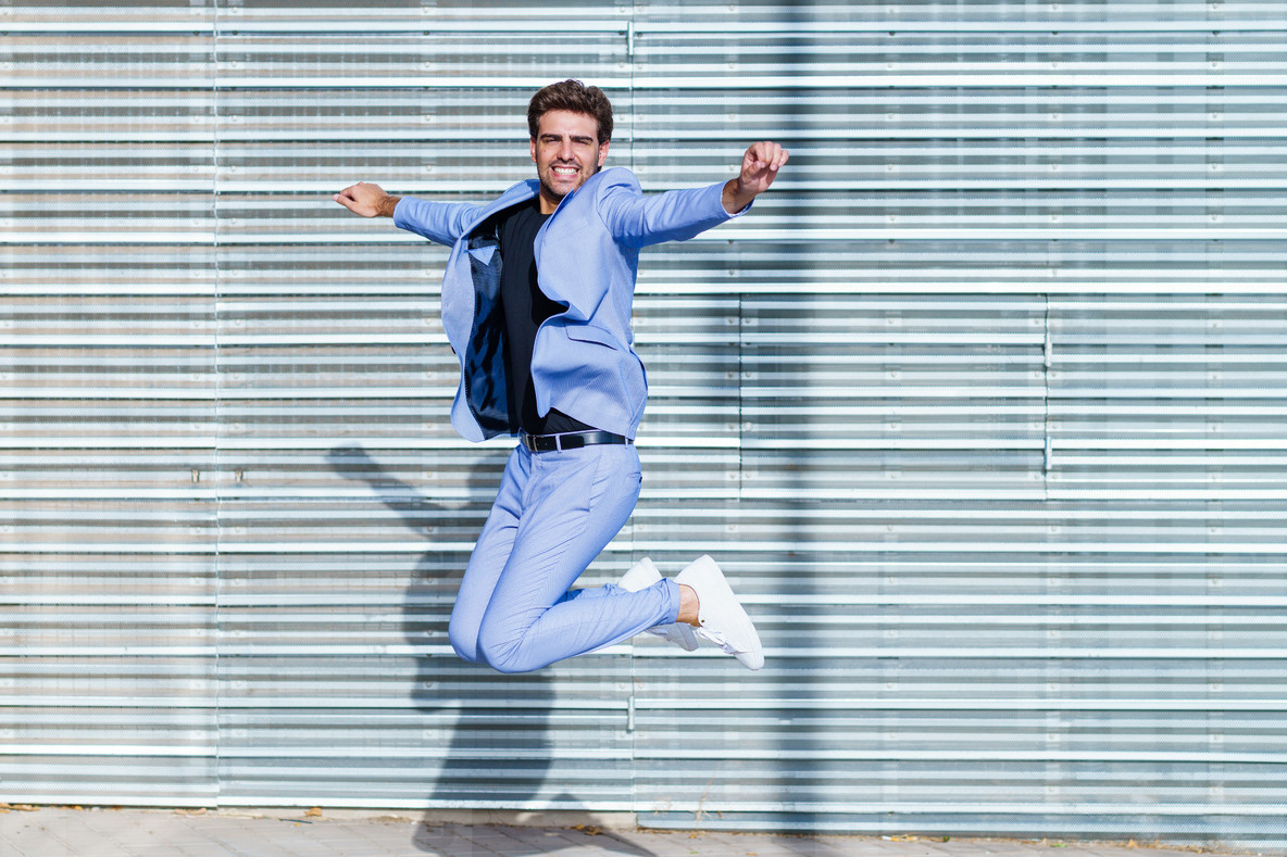 Young man wearing a suit jumping outdoors