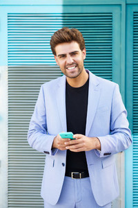 Young businessman wearing blue suit using a smartphone in urban background