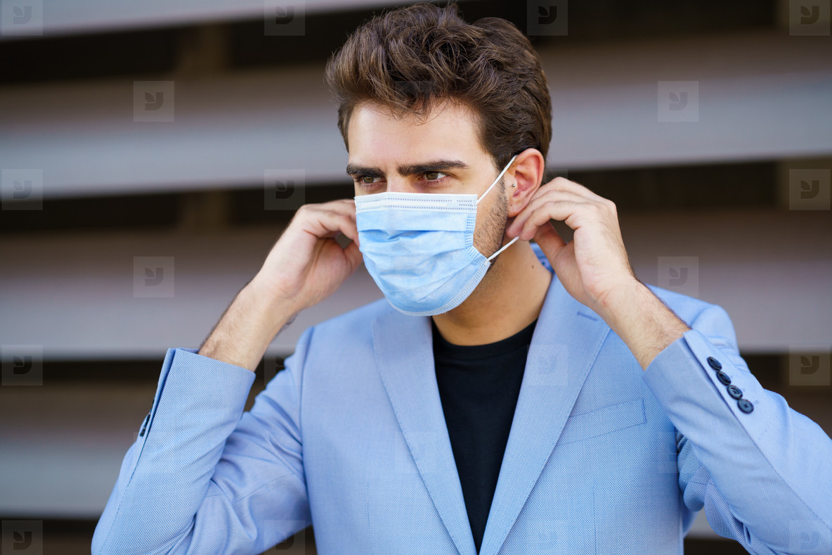 Businessman putting on a surgical mask to protect against the coronavirus