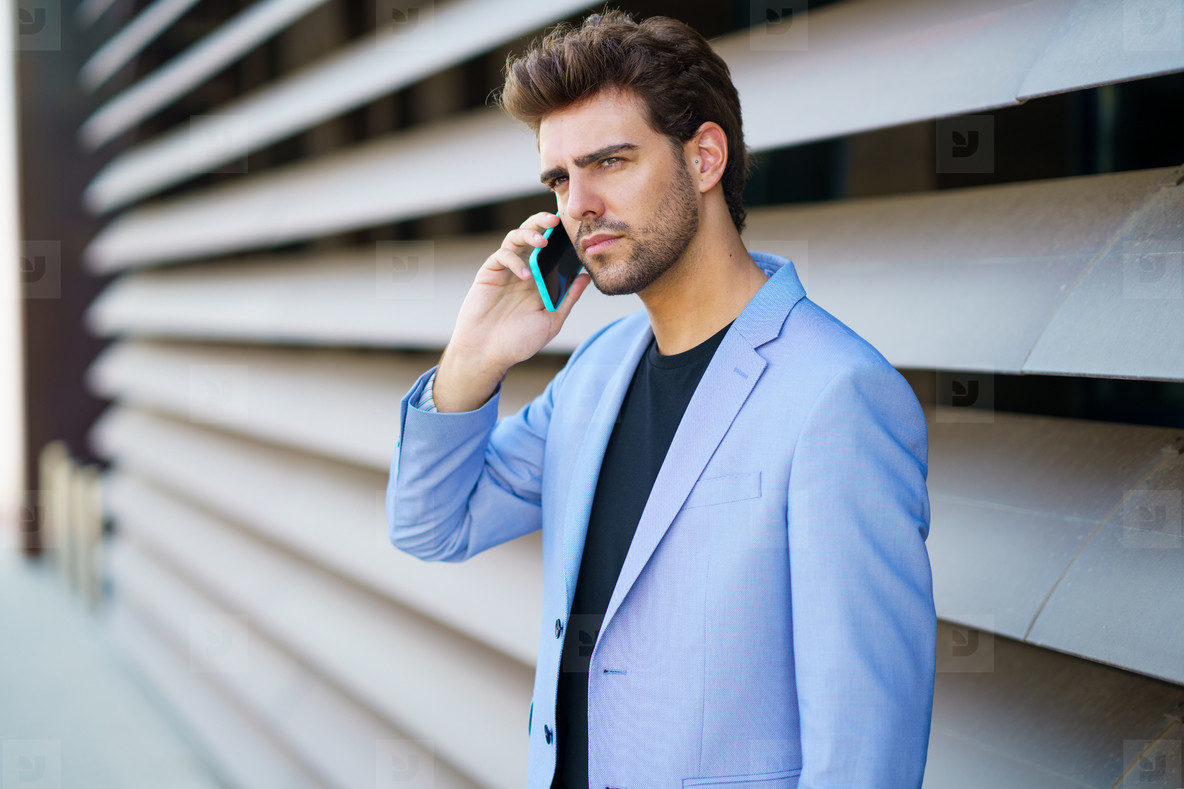 Businessman talking to his smartphone wearing blue suit