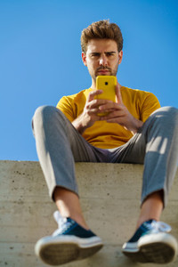 Man using his smartphone sitting on a ledge outside