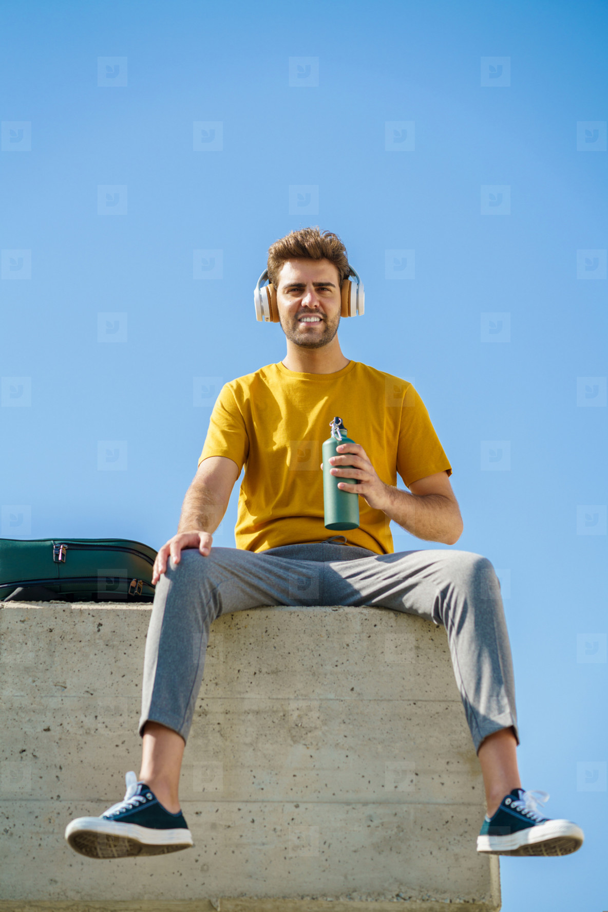 Male sitting outside using an aluminum water bottle  headphones and backpack