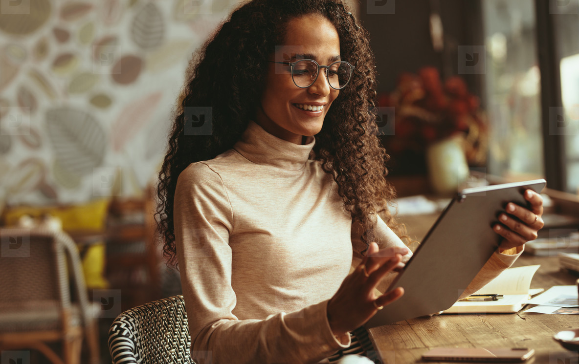 Woman using her digital tablet at cafe