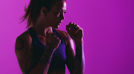 Close up portrait of fit woman on purple background