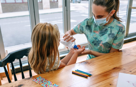 Mother applying disinfectant gel to daughter