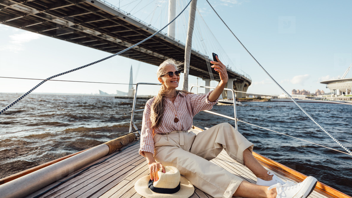 Happy mature woman on yacht trip