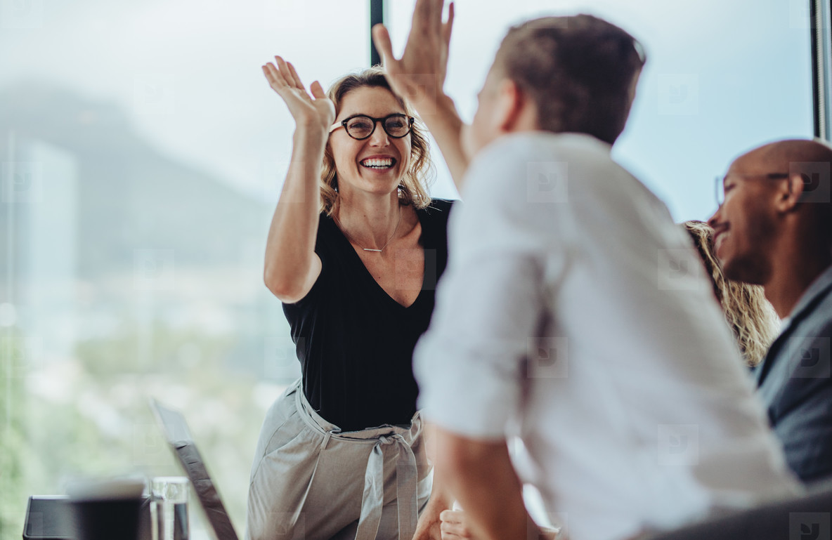 Businesswoman giving a high five to a colleague in meeting