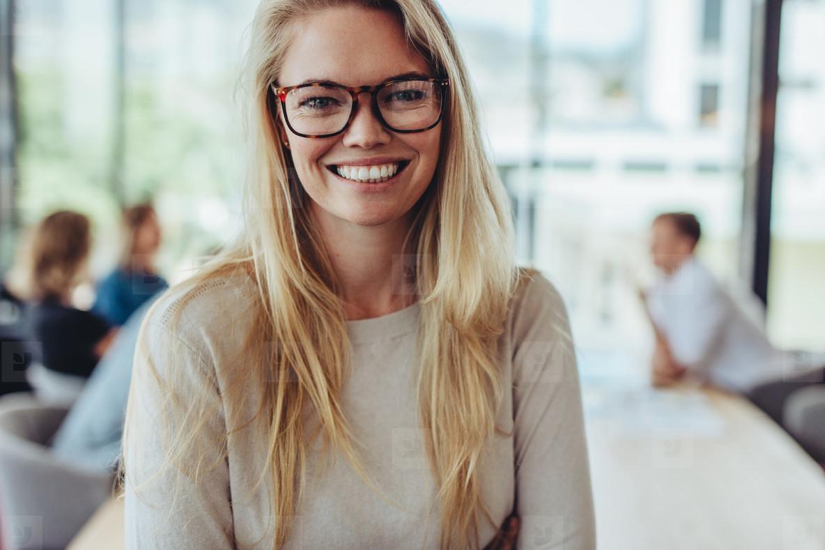 Portrait of happy businesswoman in boardroom
