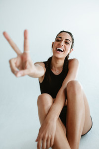 Cheerful sports woman gesturing peace sign