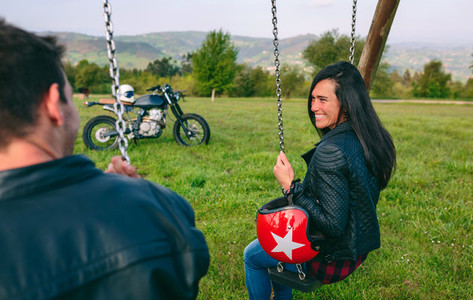 Happy young woman looking at her boyfriend sitting on a swing