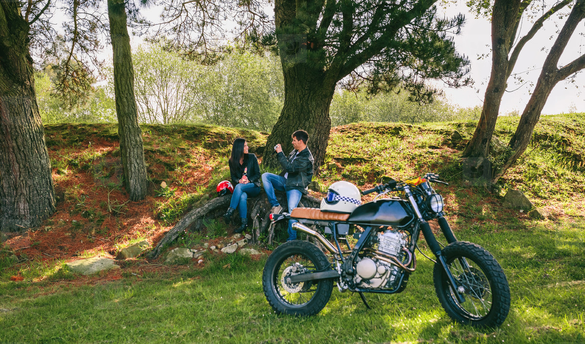 Couple resting from a motorcycle trip taking picture