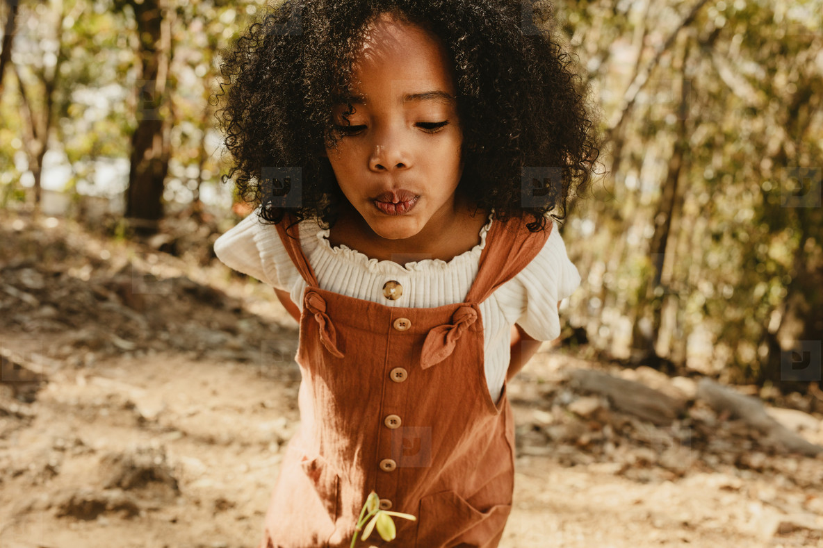 Girl blowing air on a flower in forest