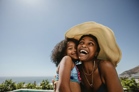 Woman with her daughter having fun at the poolside
