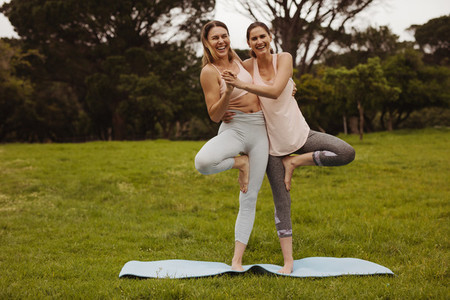 Happy friends having fun during yoga workout