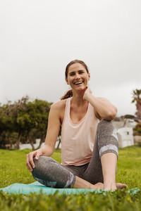 Portrait of a smiling woman sitting in park