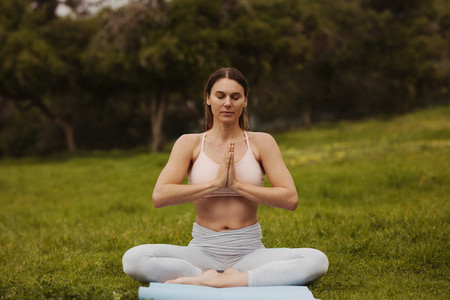Woman sitting in park doing yoga