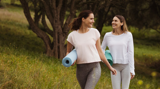 Fitness women walking in park with yoga mats