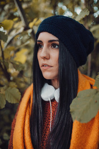 Brunette woman portrait with her headphones in the forest