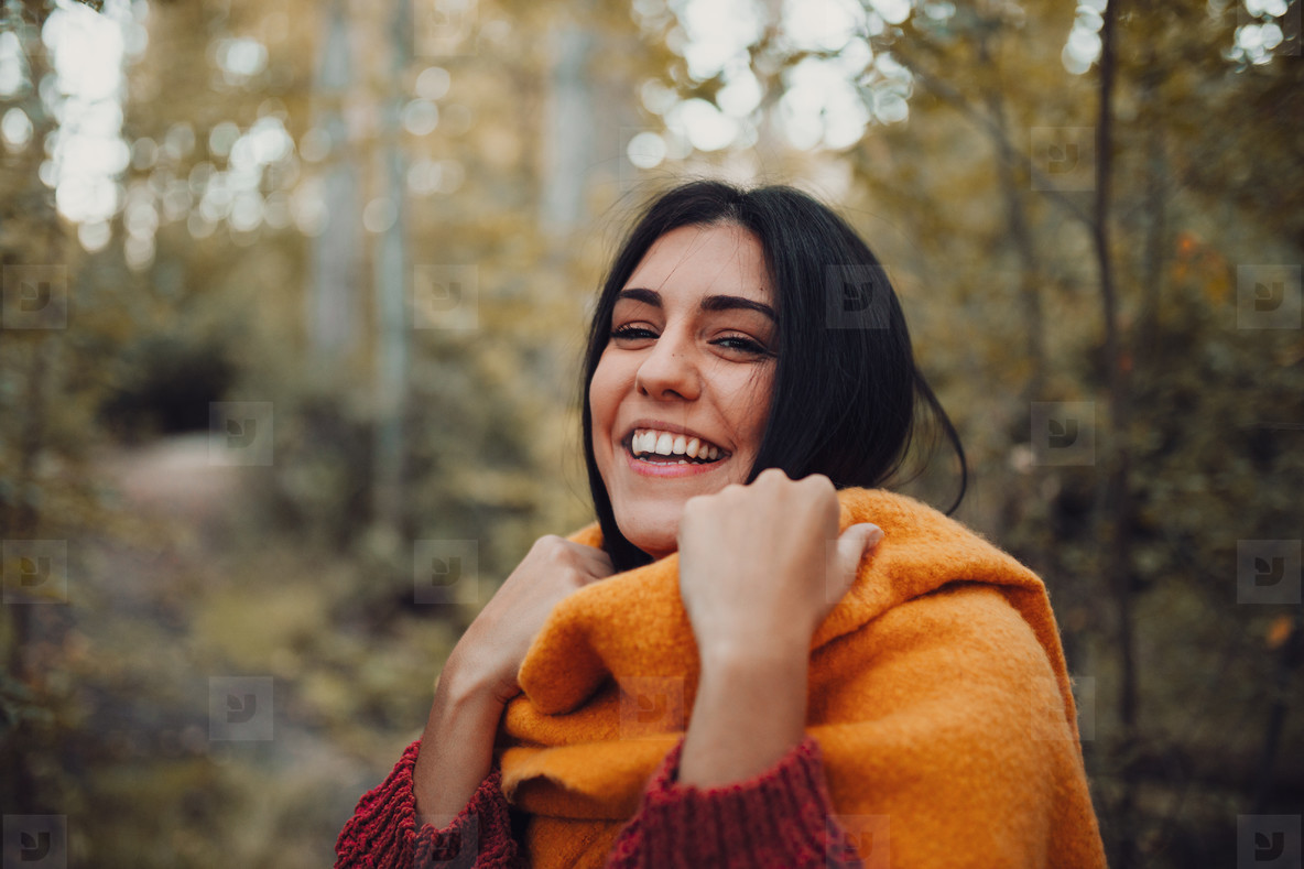 Woman dresses with her scarf inside the forest