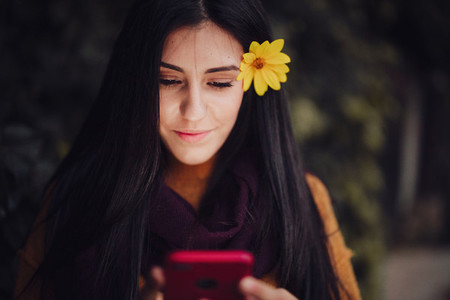 Woman using her phone with flower in her hair