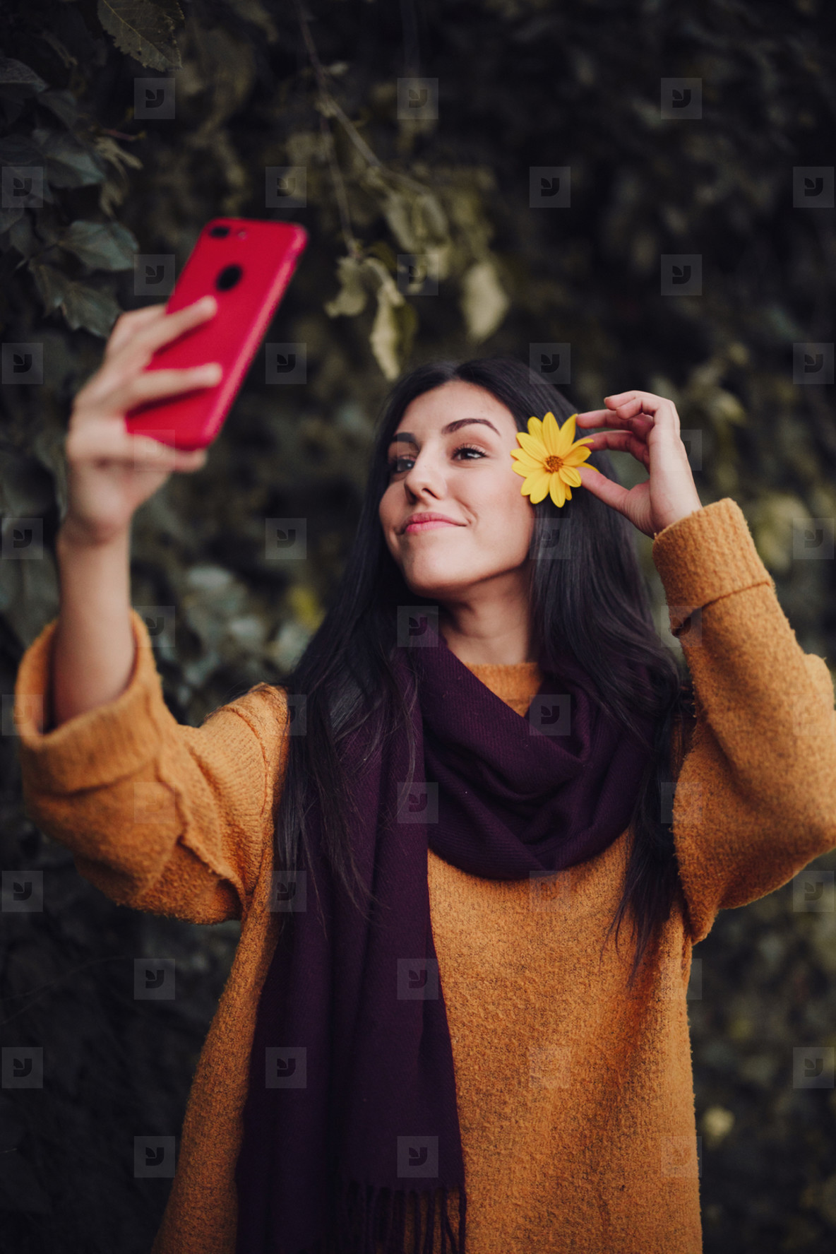 Woman taking a selfie with her phone with flower in her hair