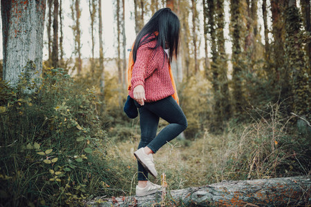 Woman walking on a trunk through the forest during the day