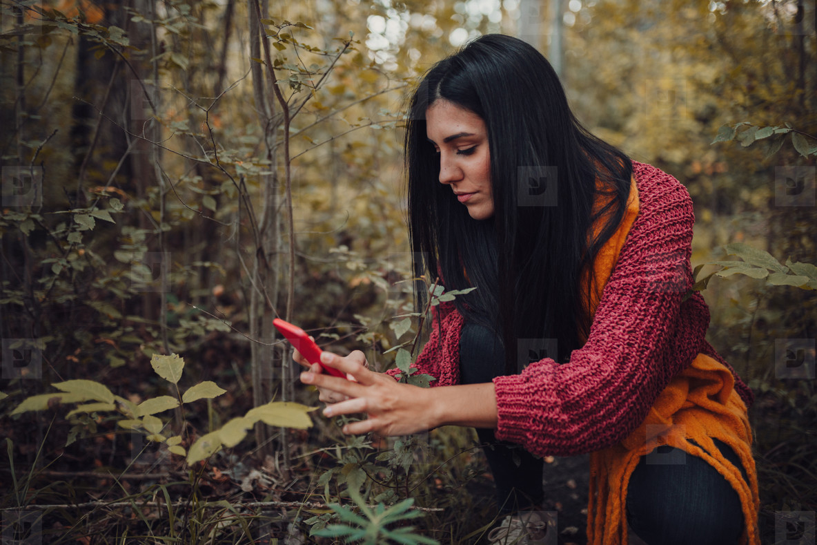 Woman taking photos with her phone through the forest